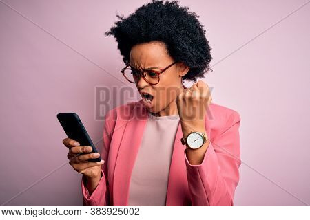 Young African American afro woman with curly hair having conversation using smartphone annoyed and frustrated shouting with anger, crazy and yelling with raised hand, anger concept