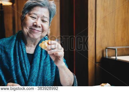 Old Asian Elderly Senior Elder Woman Eating Bread At Restaurant. Mature Lifestyle