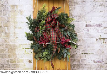 A Colorful Holiday Wreath On A Wooden Sled Leaning Against A White Brick Wall On A Building Exterior