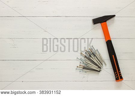 Hammer With A Rubberized Orange And Black Handle And Stack Of Dowel Nails On White Wooden Background