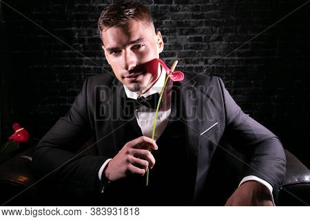 Portrait Of Handsome Stylish Man Wearing A Tuxedo Holding Up Glass Of Sparkling Wine And Looking At