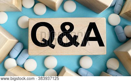 Questions And Answers On Wooden Cube Blocks On Grey Background With Scattered Blue Pills From A Whit