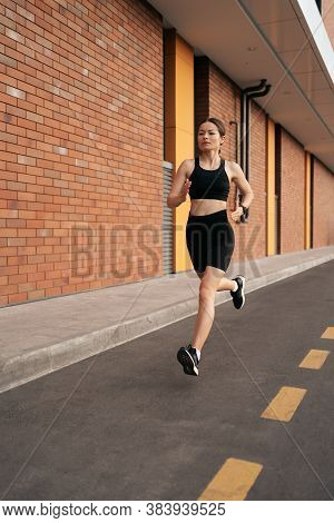 Young Woman Sprinting In The Morning Outdoors. Female Runner Working Out In The City.