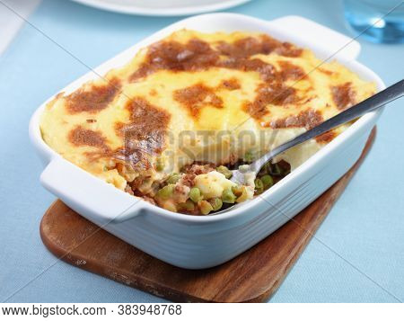 Cottage pie with carrot and peas in a pottery baking dish on the blue napkin. Traditional English dish with crusty top and juicy filling