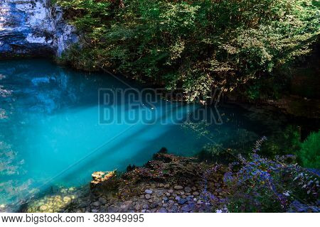 Beautiful Blue Clear Emerald Lake, Glowing In The Sun, Pond Near A Rocky White Crag
