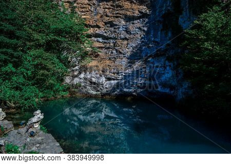 Beautiful Blue Clear Emerald Lake, Glowing In The Sun, Pond Near A Rocky Cliff Crag And Trees