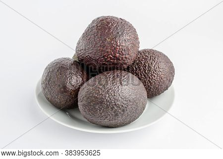 Four Ripe Ready To Eat Avocado Fruits On A White Plate On A White Table