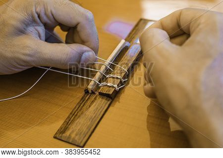 Male hands changing the strings of a classical guitar Luthier putting nylon strings on a Spanish cla