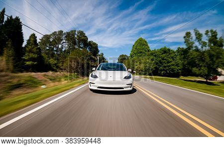 Raleigh, Nc Usa, April 17, 2020: A New Tesla Model 3 All Electric Vehicle Driving Down A Country Roa