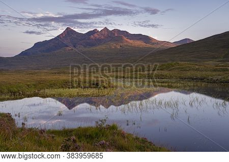 Panoramic View Of Cuillin Mountain Range Reflected In Calm Water Of A Small Loch Nan Eilean On Isle