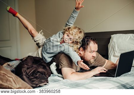 Work From Home With Kids Children. Father Working On Laptop In Bedroom With Child Daughter On His Ba