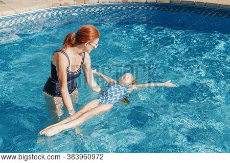 Red-haired Caucasian Mother Training Daughter To Swim In Swimming Pool Outdoor. Mom Teaching Girl To