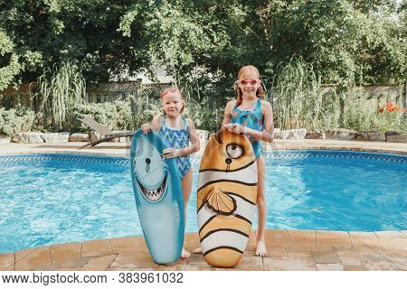 Cute Smiling Caucasian Girls Sisters Friends Standing By Pool With Swim Boards At Home Backyard. Chi