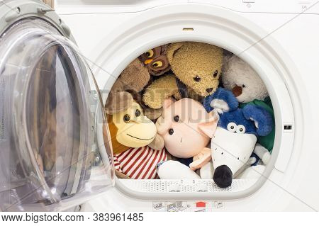 Baby toys in the tumble dryer. Soft baby toys after washing and drying in laundry room.