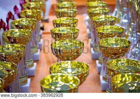 Beautiful Gold Cup On The Background Of Cups For Awarding. Prizes For Winners, A Collection Of Gold-