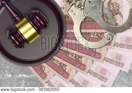 100 Russian Rubles Bills And Judge Hammer With Police Handcuffs On Court Desk. Concept Of Judicial T