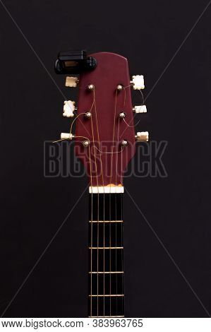 Guitar Tuner. Wooden Guitar On A Black Background. Guitar Tuning. The Guy Tunes The Guitar.