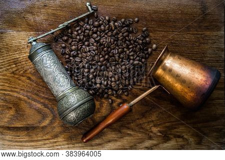 Turkish Coffee Concept. Copper Pot (cezve), Vintage Coffee Grinder, Coffee Beans On A Dark Wooden Ba