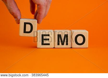 Concept Word 'demo' On Cubes On A Beautiful Orange Background. Male Hand. Business Concept. Copy Spa