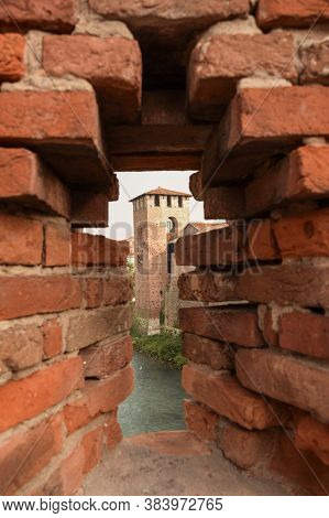 A Brick Embrasure Of A Medieval Castle, Through Which The High Tower Of The Fortress Is Visible. The