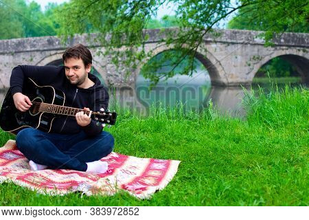 Man Playing Acoustic Guitar On The Bank Of Bosna River. Roman Bridge In The Background