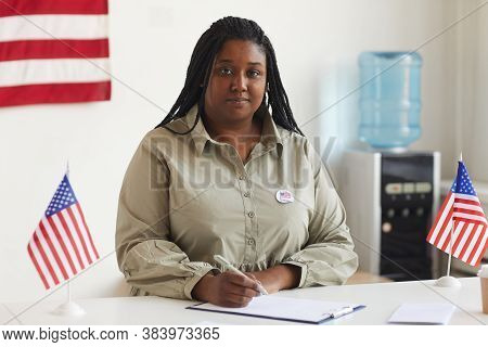 Portrait Of Smiling African-american Woman Working At At Polling Station On Election Day And Registe