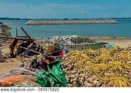 Small Fishing Boat Filled With Nets And Gear Beached Among Assortment Of Fishing Paraphernalia.