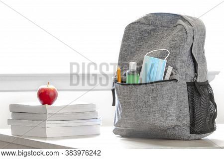 Student School Bag Pack With Sanitizer, A Face Mask, Pencils, Books And An Apple On A Table. Back To