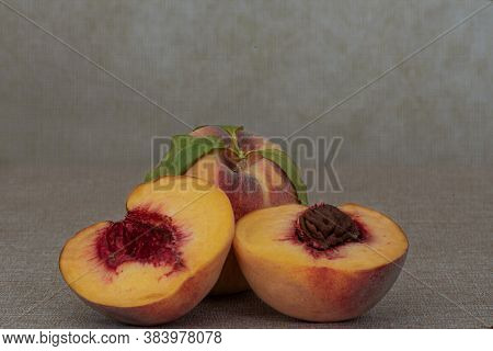 Two Fresh Yellow Peaches On Brown Table, One Whole And One Cut In Half, Centered, With Macro Detail