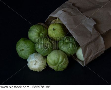 Tomatillos Spilling From A Paper Bag That Is Turned Over, On Black Background- California Produce Co