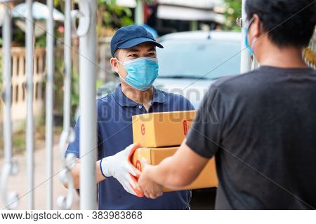 Delivery Asian Man Holding Cardboard Boxes In Medical Rubber Gloves And Mask. Online Shopping And Ex