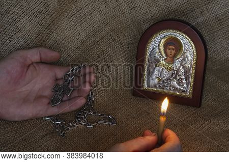 Male Hands Hold A Pectoral Cross And A Burning Candle In Front Of A Christian Icon. Icon Of The Arch