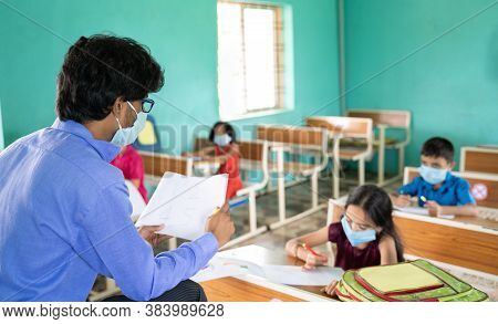 Teacher In Medical Mask With Limited Kids Teaching At Classroom While Maintaining Social Distance Du