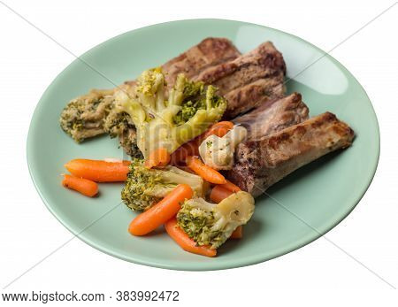 Grilled Pork Ribs With Broccoli Cabbage, Carrots And Garlic On A Plate. Fried Pork Ribs With Vegetab