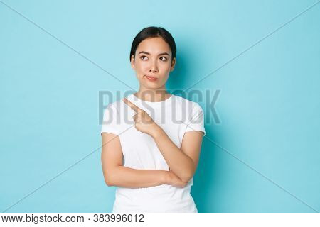 Lifestyle, Beauty And Shopping Concept. Skeptical And Unamused Asian Woman In White T-shirt Pointing