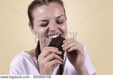 The Girl Tastes Chocolate. The Girl Is Enjoying The Taste Of Chocolate. Delight In The Taste Of Choc
