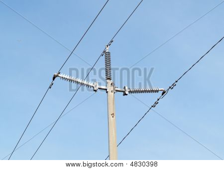 High Tension Electrical Lines And Pole Against Blue Sky