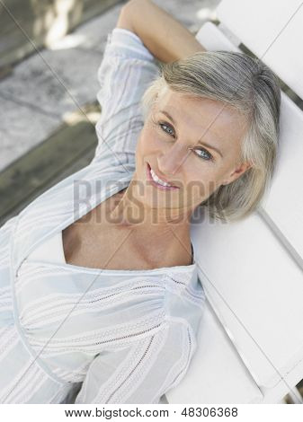 Elevated view of a smiling middle aged woman reclining on sunlounger