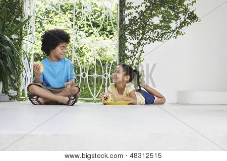 Full length of young brother and sister having breakfast on porch