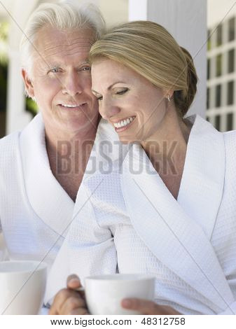 Middle aged couple in bathrobes with coffee cups sitting on verandah