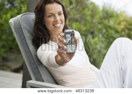 Smiling young woman holding up picture message on porch