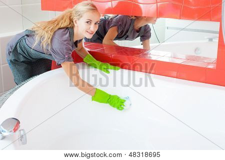 Woman cleaning bath at home. Female washing bathtub. Tub