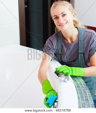 Woman cleaning bath at home. Female washing bath