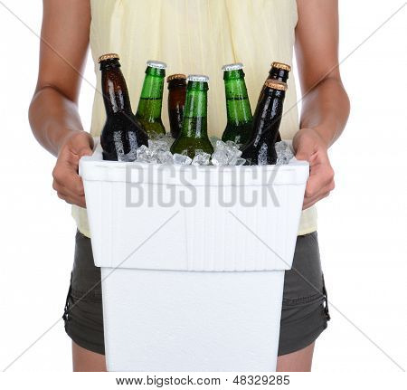 Closeup of a young woman carrying a styrofoam ice chest, over a white background. Cooler is full of ice and beer bottles. Woman is unrecognizable.