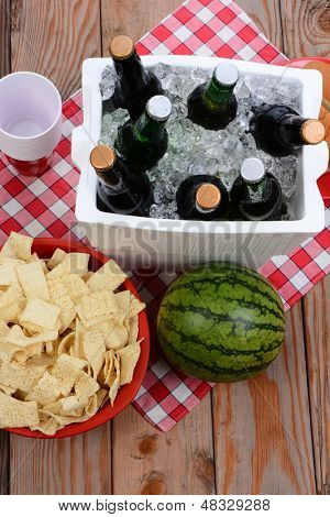 High angle shot of a picnic spread on a wood deck with red and white checkered table cloth. Items include: beer, ice chest, cups, chips and watermelon