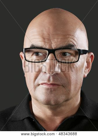 Closeup of bald middle aged man wearing glasses on black background