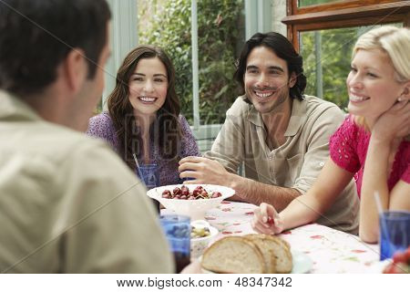 Group of four multiethnic young people sitting at verandah table