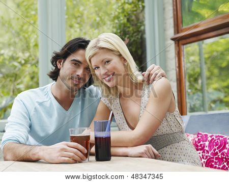 Portrait of a young multiethnic couple sitting at verandah table