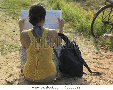 Rear view of a young woman sitting in dirtroad with backpack and map