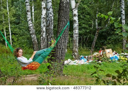 Young barefooted woman with discontented face lies in hammock at birchwood near pile of garbage
